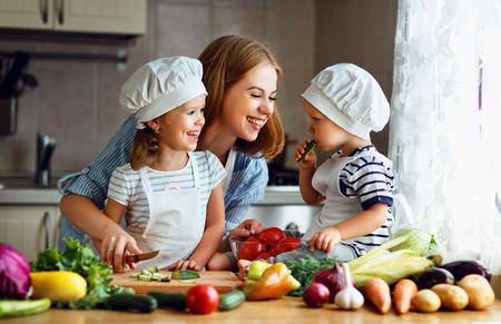 Une alimentation saine. Joyeuse famille mère et enfants prépare la salade de légumes dans la cuisine Banque d'images - 82592572