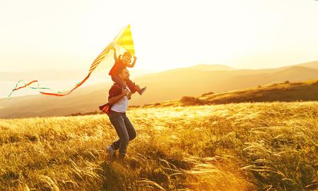 Heureux père de famille et fille d'enfant courir avec un cerf-volant sur la prairie Banque d'images - 82592577