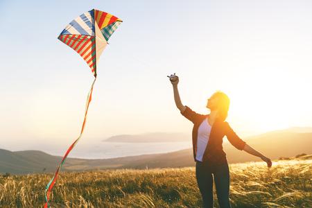 Gelukkige jonge vrouw die bij een zonsondergang in de zomer met een vlieger loopt