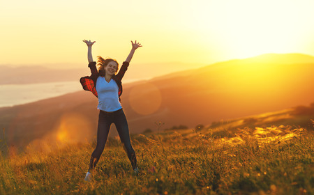 Happy woman with open hands dances, jump,  rejoices, laughs  on sunset in nature