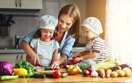 Healthy eating. Happy family mother and children prepares vegetable salad in kitchen