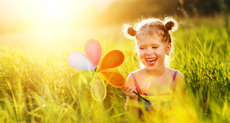 Happy child girl with colorful pinwheel windmill in summer outdoors