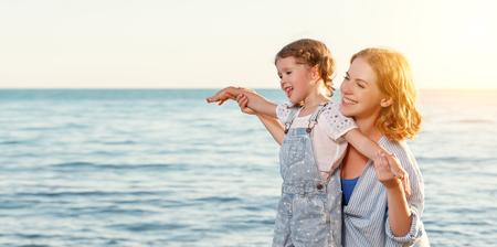 ビーチで幸せな家族。母ハグ子娘 写真素材