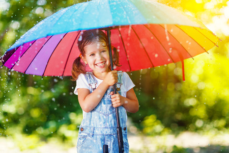 Happy child girl laughs and plays under the summer rain with an umbrella  版權商用圖片