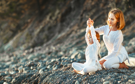 Happy family mother and child daughter doing yoga, meditate in lotus position on beach at sunset