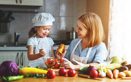 Healthy eating. Happy family mother and child  girl preparing vegetarian vegetable salad at home in kitchen