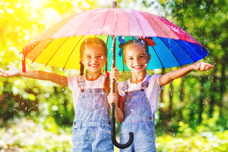 Happy funny  sisters twins  child by girl with a multicolored umbrella  laughing Stock Photo