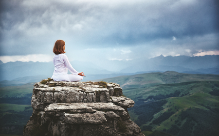 woman practices yoga and meditates in the lotus position on mountains, peak Stock Photo