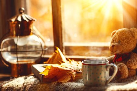 秋の静物。ウィンドウ、熱いお茶マグカップ本とテディベア