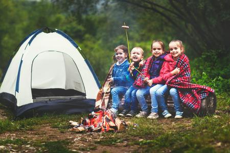Kinderen lachen en bakken worstjes op het spel bij een tent in een wandeling