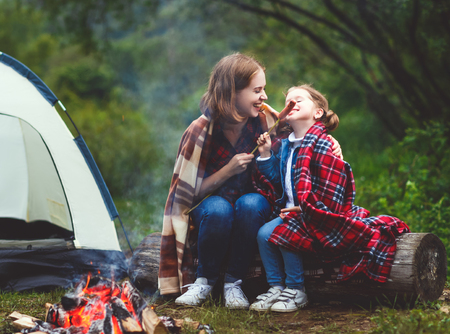 Happy tourist family on a journey hike. mother and child fry sausages on bonfire near the tent photo