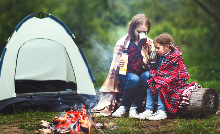 Family mother and child daughter drinking tea  on a camping trip with a tent and by the bonfire photo