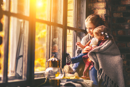 happy family mother and baby son in autumn window photo