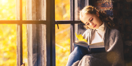 Happy woman reading a book by the autumn window photo
