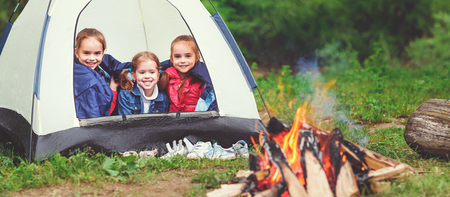 Childrens tourism. Happy kids  girls in campaign in a tent near fire Reklamní fotografie