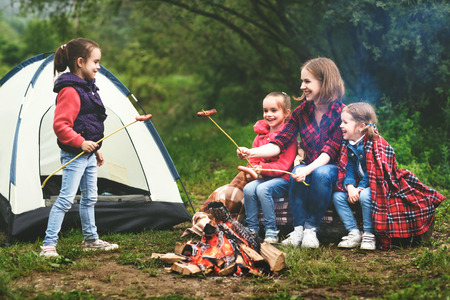 Happy tourist family on a journey hike. mother and children fry sausages on bonfire near the tent 스톡 콘텐츠