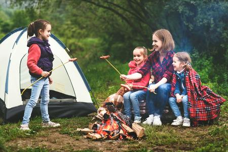 Glückliche Touristenfamilie auf einer Wanderung. Mutter und Kinder braten Wurst am Lagerfeuer in der Nähe des Zeltes