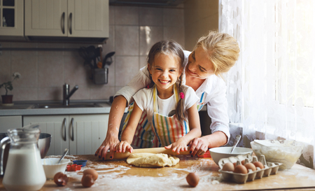 Happy family mother and child daughter bake kneading dough in the kitchen photo