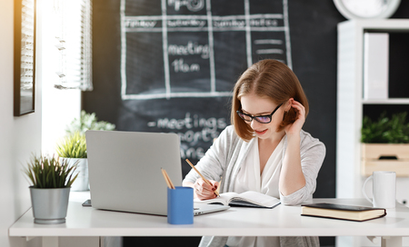 Happy businesswoman woman with computer and mobile phone photo