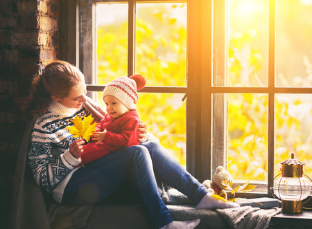 happy family mother and baby son in autumn window Stock Photo