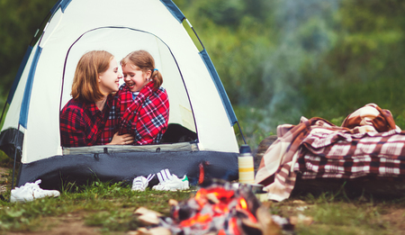 Family mother and child daughter on a camping trip with tent and by the bonfire photo