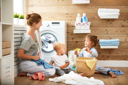 domestic: Happy family mother  housewife and children in the laundry load a washing machine
