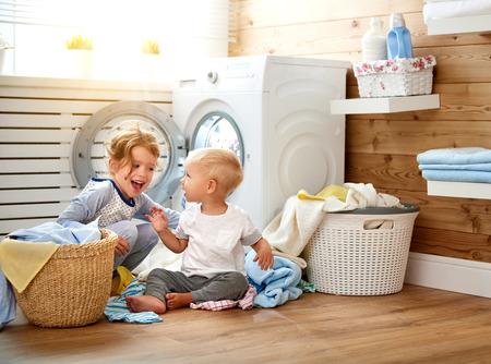 Gelukkige kinderen jongen en meisje in de wasgoed laad een wasmachine Stockfoto