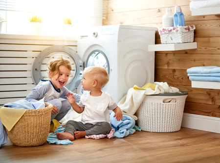 Happy children boy and girl in   in the laundry load a washing machine Standard-Bild