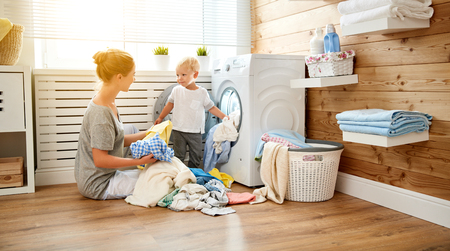 Happy family mother  housewife and children in the laundry load a washing machine photo