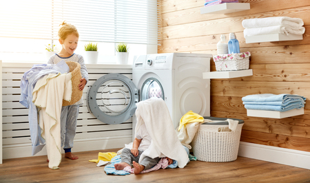 bath: Happy children boy and girl in   in the laundry load a washing machine Stock Photo