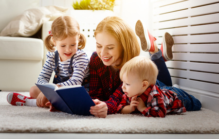 Mother reads book to children son and daughter photo