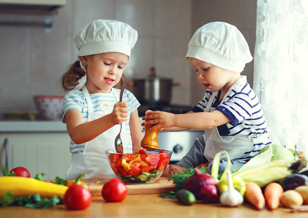 Healthy eating. Happy children prepares and eats vegetable salad in kitchen photo