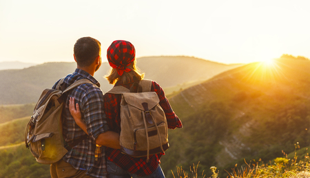 happy couple man and woman tourist at top of mountain at sunset outdoors during a hike in summer photo
