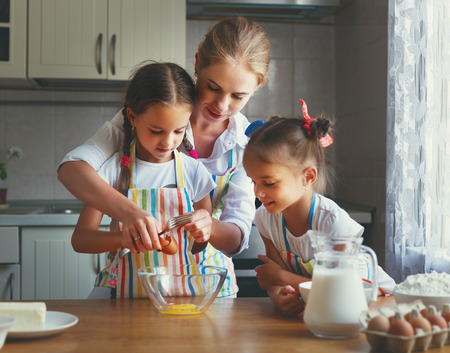 Happy family mother and children twins daughter bake kneading dough in the kitchen photo