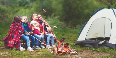 아이들은 하이킹에서 텐트 근처의 스테이크에서 웃음과 소시지를 볶는다. 스톡 콘텐츠