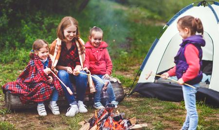 Gelukkige toeristische familie op een reiswandeling. Moeder en kinderen braden worstjes op het vuur in de buurt van de tent Stockfoto