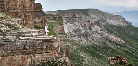 woman practices yoga and meditates   on mountains, peak Stock fotó - 84469111