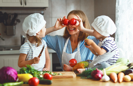 Healthy eating. Happy family mother and children  prepares   vegetable salad in kitchen photo