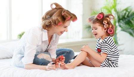 happy Mother and child daughter in hair curlers paint nails, make a pedicure