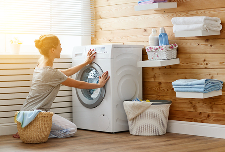 Een gelukkige huisvrouw vrouw in wasruimte met wasmachine Stockfoto