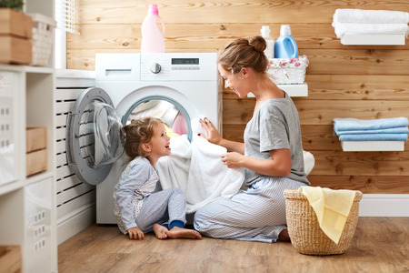 Happy family mother housewife and child daughter in laundry with washing machine  Foto de archivo