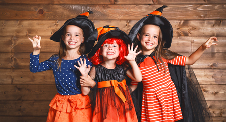 Laughing funny children sister twins  girl in a witch costume in halloween  Stock Photo