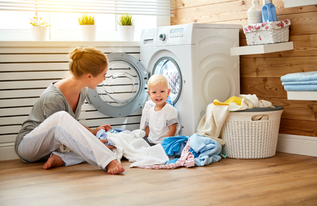 Happy family mother housewife and children in the laundry Stock Photo