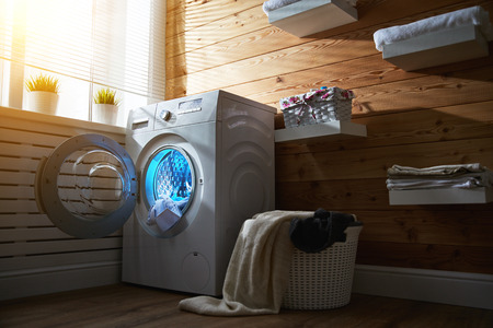 sink: Interior of a real laundry room with a washing machine at the window at home