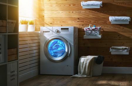 Interieur van een echte wasruimte met een wasmachine bij het raam thuis Stockfoto