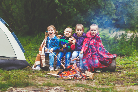 Children laugh and fry sausages at the stake near a tent in a hike
