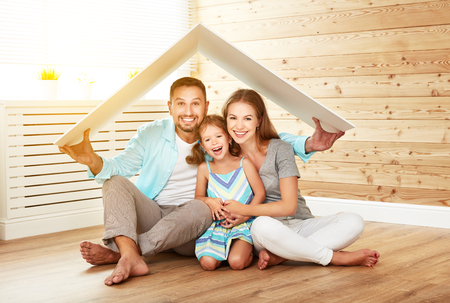 Concept housing a young family. Mother, father and child in new house with a roof Stockfoto