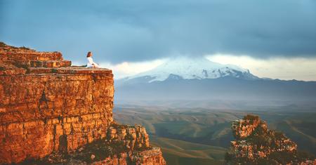 여자는 요가를 연습하고 산에서 명상을합니다.