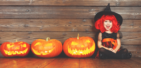 happy child girl in costume witch for Halloween with pumpkins with burning eyes on   wooden background