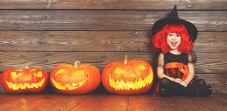 Gelukkig kind meisje in kostuum heks voor Halloween met pompoenen met brandende ogen op houten achtergrond Stockfoto